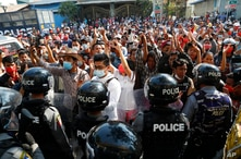 Residents and protesters face riot police as they question them about recent arrests made in Mandalay, Myanmar, Saturday, Feb…