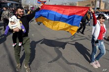 Supporters of Armenian Prime Minister Nikol Pashinyan march with Armenian national flags toward the main square in Yerevan,…