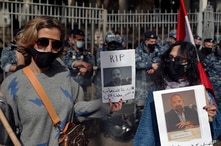 Anti-Hezbollah protesters hold pictures of Lokman Slim, a longtime Shiite political activist and researcher, who has been found…
