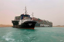 In this photo released by the Suez Canal Authority, a boat navigates in front of a massive cargo ship, named the Ever Green,…