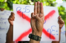 An anti-coup protester shows the three fingered salute of resistance during a strike walk with slogans to show their…