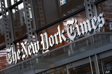 FILE - In this Thursday, May 6, 2021 file photo, a sign for The New York Times hangs above the entrance to its building, in New…