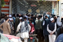 Afghans wait for hours to try to withdraw money, in front of Kabul Bank, in Kabul, Afghanistan, Saturday, Aug. 28, 2021. (AP…