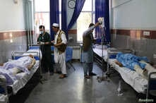 Afghan men receive treatment at a hospital after a bus was hit by a roadside bomb in Herat province, western Afghanistan, July 31, 2019.