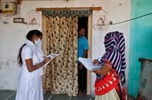 Health workers collect personal data from a man as they prepare a list during a door-to-door survey on the outskirts of Ahmedabad
