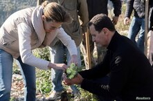 Syria's President Bashar al-Assad and his wife Asma, plant trees in city of Draykish