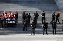 People are detained on the steps of the U.S. Capitol Building during a demonstration against planned Trump administration cuts…