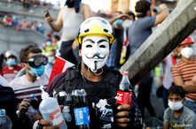 An Iraqi demonstrator caries bottles of soda used to neutralise tear gas during an anti-government protest in Baghdad, Iraq…