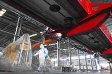 A worker in protective suit disinfects a factory before it resumes operation on February 10 following an extended Lunar New…