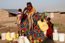 A Turkana woman washes her face at a water point within Kalobeyei Settlement outside the Kakuma refugee camp in Turkana county,…