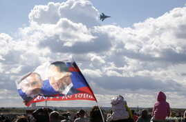 A spectator waves a flag depicting images of Russian President Vladimir Putin (L) and Prime Minister Dmitry Medvedev as a Sukhoi SU-34 fighter-bomber performs during the MAKS International Aviation and Space Salon in Zhukovsky outside Moscow, Russia,