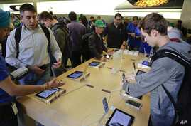 Visitors to the Apple store examine the iPhone 6 and 6 Plus, Sept. 19, 2014,  in New York.