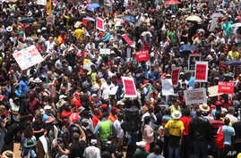 Hundreds of demonstrators gather at the end of a protest march across the Nelson Mandela bridge into Johannesburg, Dec. 16, 2015. The protesters were calling for President Jacob Zuma to be removed.
