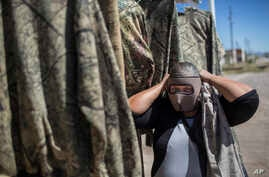 A vendor shows a mask used by migrants as protection from the low desert night temperatures they face during their treks to the United States, in Sonoyta, in the northern Mexican state of Sonora, April 4, 2017.