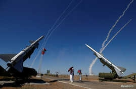 People watch S-300 air defense missile systems launching missiles during the Keys to the Sky competition.