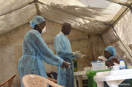 FILE - Health workers take blood samples for Ebola virus testing at a screening tent in the local government hospital in Kenema, Sierra Leone, June 30, 2014.