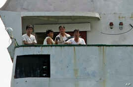 North Korean sailors look out from the deck of their cargo ship Chong Chon Gang in Sherman Bay near Colon City, Panama, Wednesday, Feb. 12, 2014