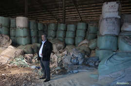Kittisak Ratanawarahal, chairman of the Northern Farmers Network, stands in warehouse of rotten rice abandoned ten years ago in Phichit province under price-support scheme by then-prime minister Thaksin Shinawatra Feb. 6, 2014.