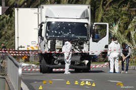 Investigators continue to work at the scene near the heavy truck that ran into a crowd at high speed killing scores who were celebrating the Bastille Day, July 14 national holiday on the Promenade des Anglais in Nice, France, July 15, 2016.