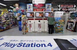 FILE - A man tries out Nintendo Co Ltd's 3DS portable game console near an advertisement for Sony's PlayStation 4 game console at an electronics retail store in Tokyo, May 7, 2014.