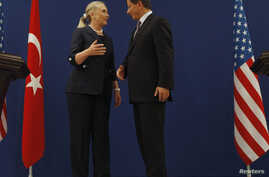 U.S. Secretary of State Hillary Clinton and Turkish Foreign Minister Ahmet Davutoglu talk after their news conference in Istanbul, Turkey, August 11, 2012.