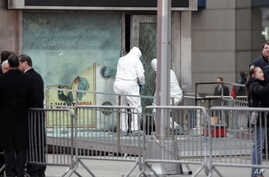 FILE - NYPD bomb squad unit inspects damage done by an explosive at military recruitment center in Times Square, March 6, 2008.
