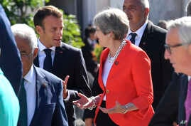 French President Emmanuel Macron (L) talks with British Prime Minister Theresa May when arriving for a family photo at the informal EU summit in Salzburg, Austria, Sept. 20, 2018.