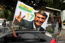 A supporter of Brazil's new president-elect, Jair Bolsonaro, celebrates in front of Bolsonaro's condominium at Barra da Tijuca neighborhood in Rio de Janeiro, Brazil, Oct. 29, 2018.