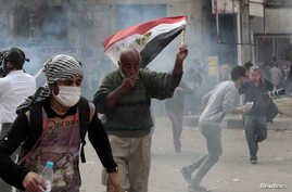 Anti-Mursi protesters run for cover during clashes with riot police at Tahrir Square in Cairo, November 27, 2012.