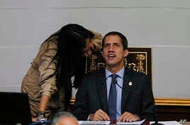 Juan Guaido, right, President of National Assembly and self-proclaimed interim president speaks with lawmaker Delsa Solorzano during a session of the National Assembly in Caracas, Venezuela, Tuesday, April 2, 2019.