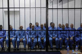 Officials of Moammar Gadhafi's government, including Abdullah al-Senussi (L), ex-spy chief in Moammar Gadhafi's government and Buzeid Dorda (2nd L), ex-intelligence chief, sit behind bars during a hearing at a courtroom in Tripoli, Libya, April 14, 2