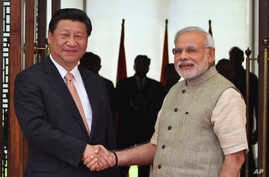 FILE - Indian Prime Minister Narendra Modi, right, shakes hand with Chinese President Xi Jinping as he welcomes him at a hotel in Ahmadabad, India, Sept. 7, 2014. The two leaders will meet April 27-28, 2018, for a visit that some experts have describ