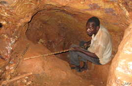FILE - A man sits in a hole he dug in the rock with makeshif tools in search for gold at the Soedoumbofor site near the eastern Cameroonian town of Batouri, June 1, 2008.
