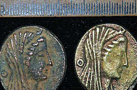 An undated handout picture released by Egypt's Supreme Council of Antiquities shows two coins dating back to the era of Ptolemy III 222-246 BC, discovered in an Egyptian oasis, south of the capital Cairo, 22 Apr 2010