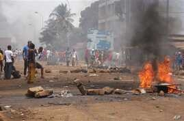 Anti government protesters burn tyres and place rocks in the streets in Conakry, Guinea, May 3, 2013