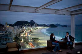FILE - Tourists sit in a bar at a hotel overlooking Copacabana beach, in Rio de Janeiro, Brazil, Aug. 16, 2013.