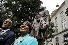 The Rev. Bernice King, right, daughter of the Rev. Martin Luther King Jr., stands under a statue paying tribute to her father, after it's unveiled on the state Capitol grounds in Atlanta, Monday, Aug. 28, 2017.