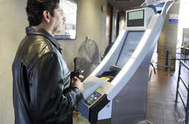 A pedestrian crossing from Mexico into the United States at the Otay Mesa Port of Entry has his facial features and eyes scanned at a biometric kiosk in San Diego, California, Dec. 10, 2015.