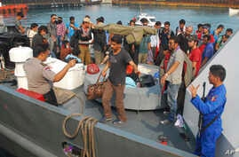 Indonesian police officers guard asylum seekers on a patrol boat upon arrival at a port in Merak, Banten province, Indonesia, Oct 12, 2012.