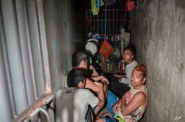 In this April 27, 2017 photo, detainees crouch on the floor inside a secret jail after being discovered by the Commission on Human Rights at Police Station 1 at Tondo district in Manila, Philippines.