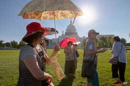 Visitors from Korea shield themselves from the early morning sun as they tour the Capitol in Washington, Aug. 12, 2016.