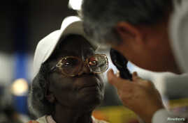 FILE - Gloria Thompson, 68, receives an eye exam at the Care Harbor/LA free clinic in Los Angeles, September 27, 2012.