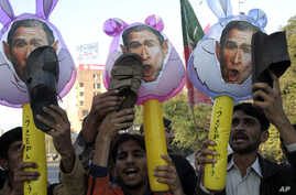 FILE - Pakistani protesters hold up shoes and caracatures of U.S. President George W. Bush during a demonstration in support of Iraqi journalist Muntadhar al-Zeidi in Lahore, Pakistan, Dec. 21, 2008.