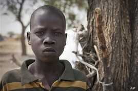 In this photo taken Saturday, Feb. 15, 2014, Ajing Abiik, 12, who fled from his hometown of Bor when the fighting broke out in December, stands next to the tree where he and his two brothers sleep in Minkaman IDP camp, Awerial County, in South Sudan.