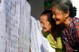 Elderly women check the name lists of parliamentary candidates at a polling station in Bali, Indonesia, Wednesday, April 9, 2014.