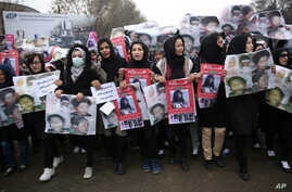 Women march in the Afghan capital of Kabul on Wednesday, Nov. 11, 2015 with pictures showing ethnic Hazaras who were allegedly killed by the Taliban, calling for a new government that can ensure security in the country.