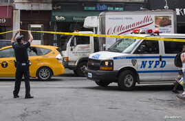 A New York police officer lifts tape to let a police vehicle through at the site of a shooting in Greenwich Village, Manhattan, New York July 28, 2014. Two U.S. Marshals and a New York City police detective were shot and wounded on Monday and a man w