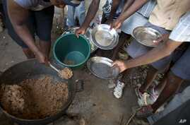 FILE - Students hold out their plates as the school cook ladles out a bulgur wheat and bean dish at a public school in Bombardopolis, Haiti. The WFP says 3.6 million Haitians face food insecurity.