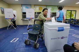 A woman casts her ballot for presidential election at a polling station in Seoul, South Korea, May 9, 2017.
