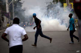 Demonstrators run from tear gas fired by police trying to disperse their protest against the government of President Michel Martelly in Port-au-Prince, Haiti, Sunday, Jan. 24, 2016. Haiti was to hold a presidential and legislative runoff election on